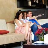Hållande ögonen på TV för ung familj Arkivbilder