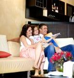 Hållande ögonen på TV för ung familj Royaltyfria Foton