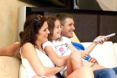Hållande ögonen på TV för ung familj Royaltyfri Foto