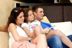 Hållande ögonen på TV för ung familj Fotografering för Bildbyråer