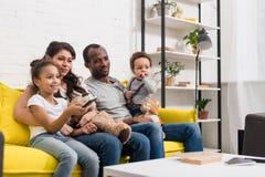 Hållande ögonen på tv för ung familj tillsammans royaltyfria foton