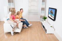 Hållande ögonen på tv för ung familj tillsammans arkivbild