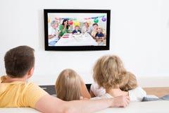 Hållande ögonen på tv för ung familj tillsammans fotografering för bildbyråer