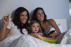 Hållande ögonen på TV för ung flicka i säng med glade kvinnliga föräldrar Arkivfoto