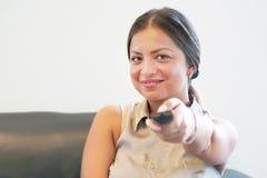 Hållande ögonen på tv för ung flicka på soffan royaltyfria foton