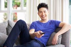 Hållande ögonen på TV för ung kinesisk man på sofaen hemma Arkivbild