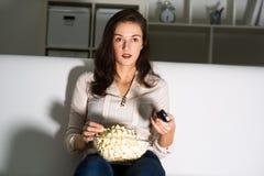 Hållande ögonen på TV för ung kvinna Royaltyfri Foto