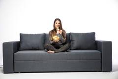 Hållande ögonen på TV för ung kvinna och ätachiper som sitter på soffan arkivfoto