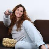 Hållande ögonen på tv för ung kvinna och ätapopcorn Royaltyfri Bild