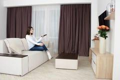 Hållande ögonen på tv för ung kvinna på soffan i vardagsrum genom att använda fjärrkontroll royaltyfria foton