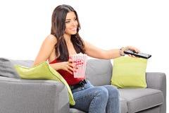 Hållande ögonen på TV för ung kvinna som placeras på en soffa royaltyfria foton