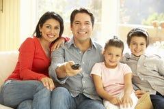 Hållande ögonen på TV för ung latinamerikansk familj hemma Royaltyfri Foto