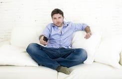 Hållande ögonen på tv för ung lycklig man som sitter den hemmastadda vardagsrumsoffan som ser kopplad av tycka om television Arkivfoton