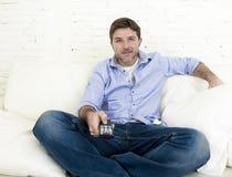 Hållande ögonen på tv för ung lycklig man som sitter den hemmastadda vardagsrumsoffan som ser kopplad av tycka om television Arkivbild