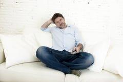 Hållande ögonen på tv för ung lycklig man som sitter den hemmastadda vardagsrumsoffan som ser kopplad av tycka om television Royaltyfri Bild