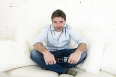 Hållande ögonen på tv för ung lycklig man som sitter den hemmastadda vardagsrumsoffan som ser kopplad av tycka om television Royaltyfri Foto
