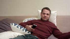 Hållande ögonen på TV för ung man i säng och drickate lager videofilmer