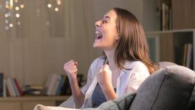 Hållande ögonen på tv för upphetsad kvinna i natten hemma lager videofilmer
