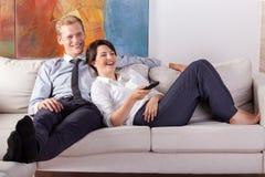 Hållande ögonen på tv för upptagna par efter arbete Royaltyfri Bild