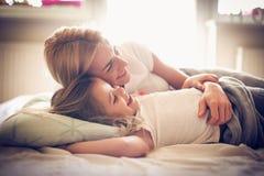 Hållande ögonen på TV med mamman i säng ballerina little Arkivfoto
