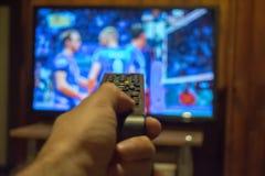 Hållande ögonen på TV och använda den avlägsna kontrollanten royaltyfri fotografi
