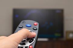 Hållande ögonen på TV och använda den avlägsna kontrollanten Arkivfoto