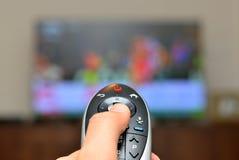 Hållande ögonen på TV och använda den avlägsna kontrollanten Royaltyfria Foton
