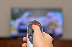 Hållande ögonen på TV och använda den avlägsna kontrollanten Arkivbilder