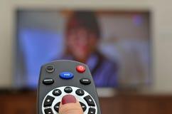 Hållande ögonen på TV och använda den avlägsna kontrollanten Royaltyfri Foto