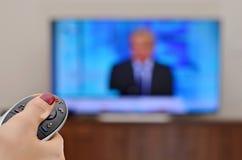 Hållande ögonen på TV och använda den avlägsna kontrollanten Arkivbild