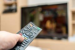 Hållande ögonen på TV och använda den svarta moderna avlägsna kontrollanten Fotografering för Bildbyråer