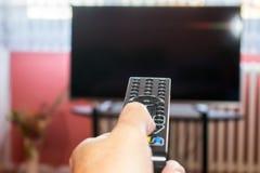 Hållande ögonen på tv och använda fjärrkontroll arkivfoto