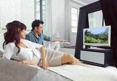Hållande ögonen på tv som ligger på säng Arkivbild