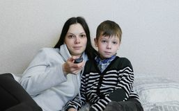 Hållande ögonen på TV som ligger på soffan Mamman och sonen håller ögonen på TV tillsammans och ler Fotografering för Bildbyråer