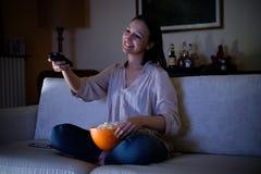 Hållande ögonen på tvsammanträde för ung kvinna på soffan royaltyfri bild