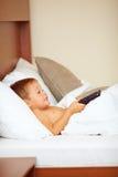 Hållande ögonen på underhållningTV-program för unge i säng Royaltyfri Foto