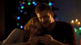 Hållande ögonen på video för härliga par på smartphonen under julgranen, intimitet arkivfoto