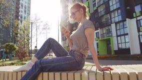 Hållande ögonen på video för Redhair kvinna på att sitta för smartphone som är utomhus- lager videofilmer