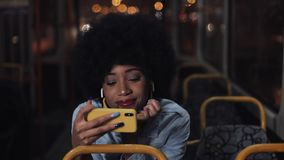 Hållande ögonen på video för ung afrikansk amerikankvinna på smartphoneridningen i kollektivtrafiken san f?r natt f?r fj?rdbroca  arkivfilmer