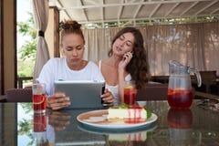 Hållande ögonen på video för ung charmig kvinna på den digitala minnestavlan, medan hennes bästa vän som har mobiltelefonkonversa Royaltyfri Bild