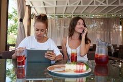 Hållande ögonen på video för ung härlig kvinna på den digitala minnestavlan, medan hennes vän som har celltelefonkonversation, Royaltyfri Fotografi
