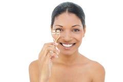 Hållande ögonfranshårrulle för gladlynt svart haired modell Royaltyfri Foto