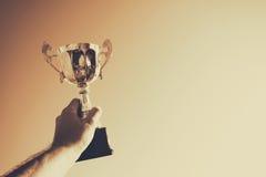 Hållande övre för man en trofékopp som en vinnare mot den blåa himlen Royaltyfria Foton