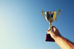Hållande övre för man en trofékopp som en vinnare mot himlen Royaltyfri Bild