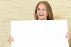 Hållande övre för nätt kvinna ett tomt vitt tecken arkivfoto