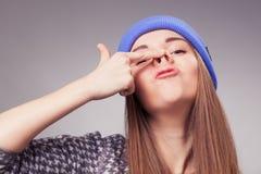 Hållande övre fingrar för ung kvinna på näsa och danandedumbomexpressi Royaltyfri Fotografi