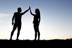 Hållande övre händer för lyckliga konturpar mot himlen på skymning arkivfoto