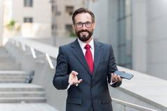 Hållande övre kreditkort för affärsman och danandeonline-betalning på hans mobiltelefon med byggnadsbakgrund royaltyfri bild