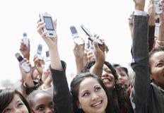 Hållande övre mobiltelefoner för folkmassa Royaltyfria Foton