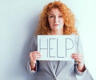 Hållande affisch för Dissapointed mitt- åldrig affärskvinna med ordet HJÄLP arkivbilder